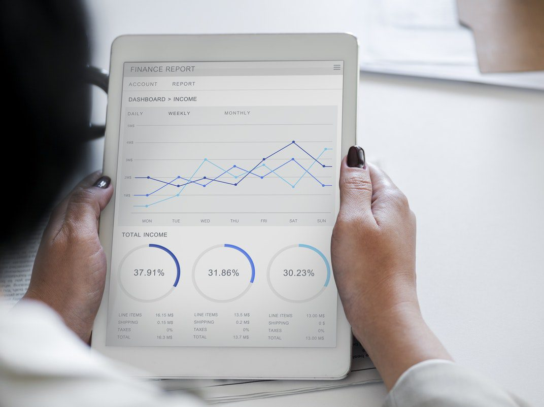 Person holding a tablet with income graph